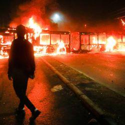 Un manifestante camina frente a autobuses en llamas durante una protesta en demanda de ayuda económica del gobierno y la aprobación del tercer retiro anticipado de fondos de pensiones en medio de la crisis desencadenada por la pandemia de COVID-19 en la comuna de Bosque, en Santiago. | Foto:Ramon Monroy / AFP