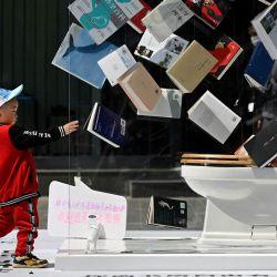 Un niño camina hacia un puesto de promoción instalado fuera de un centro comercial en el Día Mundial del Libro en Beijing. | Foto:Wang Zhao / AFP