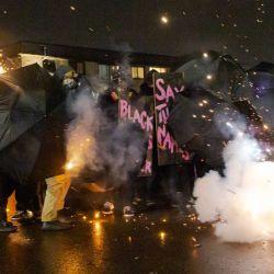 Los manifestantes se protegen con paraguas contra gases lacrimógenos y bolas de pimienta fuera de la comisaría de policía de Brooklyn Center mientras protestan por la muerte de Daunte Wright, quien fue asesinado a tiros por un oficial de policía en Brooklyn Center, Minnesota. | Foto:Kerem Yucel / AFP