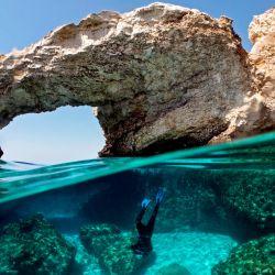 El ecólogo marino chipriota Louis Hadjioannou, de 38 años, se sumerge para fotografiar el coral, mientras monitorea el impacto del cambio climático en la delicada fauna en las aguas cristalinas de Glyko Nero en Ayia Napa, frente a la costa sureste de la isla. | Foto:Emily Irving-Swift / AFP
