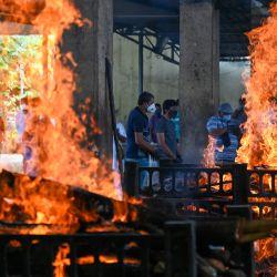 Familiares cerca de las piras de las víctimas del coronavirus Covid-19, que murieron en un incendio que mató a trece pacientes de Covid en el Hospital Vijay Vallabh en Virar. | Foto:Punit Paranjpe / AFP