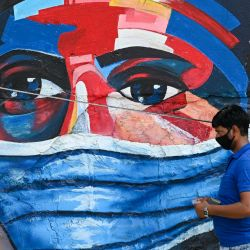 Un peatón pasa junto a un mural que muestra a una persona con una máscara protectora en Mumbai. | Foto:Punit Paranjpe / AFP