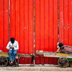 Los trabajadores descansan sentados en sus carros junto a una calle en Nueva Delhi, mientras India cerraba su capital durante una semana para tratar de controlar un brote de coronavirus. | Foto:Jewel Samad / AFP
