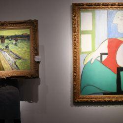 Un trabajador de la galería muestra una obra de arte titulada 'Le pont de Trinquetaille' del pintor holandés Vincent van Gogh y una obra de arte titulada 'Femme assise près d'une fenêtre (Marie-Thérèse)' del pintor español Pablo Picasso durante un photocall en Christie's casa de subastas en el centro de Londres. | Foto:Daniel Leal-Olias / AFP