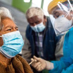 Un trabajador de la salud inocula una dosis de la vacuna Pfizer-BioNTech contra COVID-19 a una persona mayor, en un centro de vacunación en Lima. | Foto:Ernesto Benavides / AFP