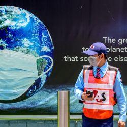 Un guardia de seguridad camina frente a un cartel que muestra a la Tierra con una mascarilla protectora en Bangkok, ya que la mayoría de los eventos que marcan el Día de la Tierra se han pospuesto debido al resurgimiento del coronavirus Covid-19 en Tailandia. | Foto:Mladen Antonov / AFP