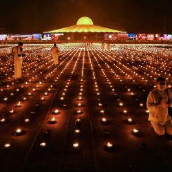 Los monjes y devotos budistas toman fotos con 330.000 velas durante un intento de romper el récord mundial Guinness de la imagen en llamas más grande durante las celebraciones del Día de la Tierra en el templo budista Wat Dhammakaya en las afueras de Bangkok. | Foto:Lillian Suwanrumpha / AFP
