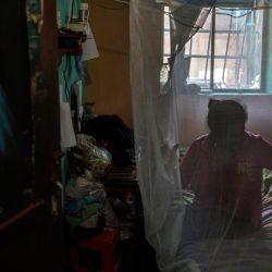 Una mujer descansa envuelta en un mosquitero para protegerse de los mosquitos que pueden transmitir la malaria en su casa de Barcelona, Estado Anzoátegui, Venezuela. | Foto:Pedro Rances Mattey / AFP
