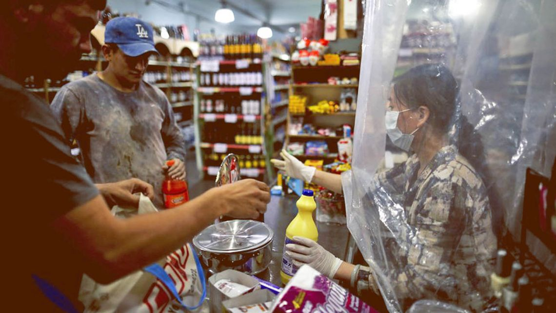 A customer is served at a supermarket in Buenos Aires, during the coronavirus pandemic.