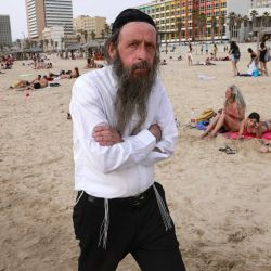 Un judío ultraortodoxo camina por una playa en la ciudad costera israelí de Tel Aviv, después de que las autoridades anunciaran que ya no se necesitaban máscaras faciales para prevenir el COVID-19 en el exterior. - Con más de la mitad de la población completamente vacunada en una de las campañas de inoculación de COVID-19 más rápidas del mundo, el número de casos de coronavirus en Israel disminuyó de algunos (Foto de menahem kahana / AFP) | Foto:AFP