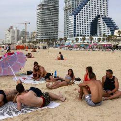 La gente se relaja en una playa en la ciudad costera israelí de Tel Aviv después de que las autoridades anunciaran que ya no se necesitaban máscaras faciales para prevenir el COVID-19 en el exterior. | Foto:AFP
