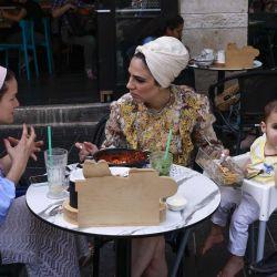 La gente come en la terraza de un restaurante en Jerusalén, después de que las autoridades israelíes anunciaran que las mascarillas para la prevención del COVID-19 ya no eran necesarias al aire libre. - | Foto:AFP
