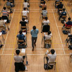 Los estudiantes de secundaria se presentan a los exámenes del diploma de educación secundaria (DSE) en Hong Kong, luego de que se les controle la temperatura y se respeten las medidas de distanciamiento social para evitar la propagación del COVID-19. | Foto:Anthony Kwan / POOL / AFP