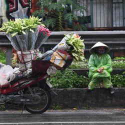 Una vendedora ambulante espera que los clientes compren flores junto a su motocicleta en Hanoi. | Foto:Nhac Nguyen / AFP