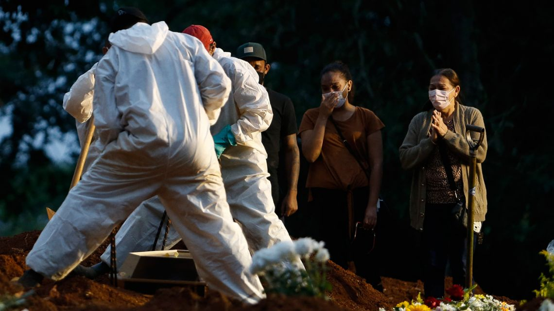 People mourn as a relative is buried by cemetery workers in protective gear as a preventive measure against the spread of the novel coronavirus disease, COVID-19, at the Vila Formosa cemetery in Sao Paulo, Brazil, on April 17, 2021. The number of people who have died worldwide in the Covid-19 pandemic has surpassed three million. The world's Covid-19 death toll surpassed three million on Saturday, according to Johns Hopkins University.
