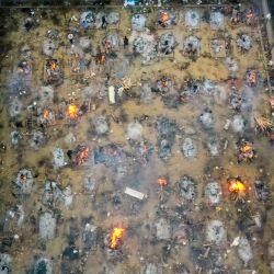 En esta fotografía aérea se ven piras en llamas de víctimas que perdieron la vida debido al coronavirus Covid-19 en un campo de cremación en Nueva Delhi. | Foto:Jewel Samad / AFP