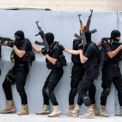 Los miembros palestinos de las fuerzas de seguridad de Hamas se protegen detrás de una pared de lona mientras realizan maniobras mientras muestran sus habilidades durante una ceremonia de graduación de la policía en la ciudad de Gaza. | Foto:Mahmud Hams / AFP