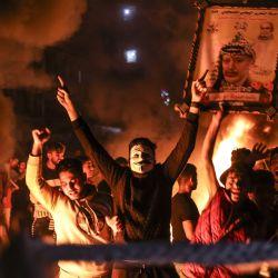 Los palestinos corean consignas mientras queman neumáticos durante una manifestación en apoyo de los manifestantes en Jerusalén en la ciudad de Gaza. | Foto:Mahmud Hams / AFP