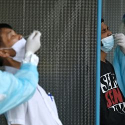 Los trabajadores médicos que usan equipo de protección personal (EPP) toman muestras de hisopos nasales para detectar el coronavirus Covid-19 en el Estadio Tailandés-Japonés, también conocido como Centro Juvenil de Bangkok, en Bangkok. | Foto:Lillian Suwanrumpha / AFP