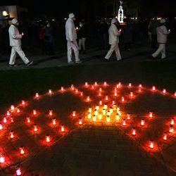 Los empleados de la planta de Chernobyl llevan velas cerca del letrero de radiactividad en el monumento a las víctimas de Chernobyl en Slavutych, la ciudad donde vivía el personal de la central eléctrica, a unos 50 kilómetros (30 millas) del lugar del accidente, durante una ceremonia conmemorativa en medio del COVID. -19 pandemia, causada por el nuevo coronavirus. | Foto:Sergei Supinsky / AFP