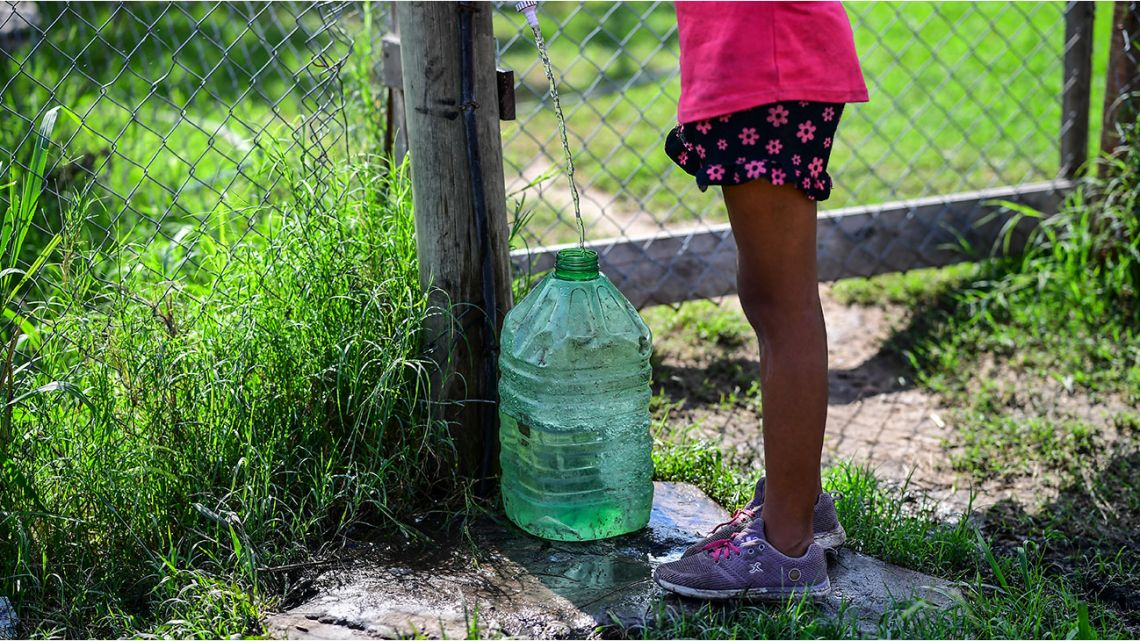 A girl fills a tank with clean water at the 28 de Octubre neighbourhood, in La Matanza municipality, Buenos Aires province, Argentina, on April 15, 2021.