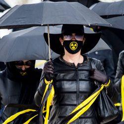 Mujeres vestidas con ropa negra y mascarillas con signo de radiactividad marchan bajo los paraguas en Minsk, para conmemorar a las víctimas del desastre nuclear de Chernobyl en el 35 aniversario de la tragedia. | Foto:AFP
