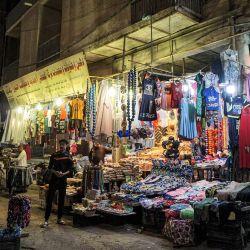 Un vendedor se encuentra junto a una tienda en un mercado cerca del santuario del Imam Ali en la ciudad santuario central de Nayaf, en Irak, durante el mes sagrado musulmán del Ramadán. | Foto:Sabah Arar / AFP