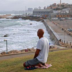 La fotografía muestra a un hombre arrodillado sobre la hierba en la antigua ciudad de Jaffa, también conocida como Yafo en hebreo y Yafa en árabe, ubicada en la orilla del mar Mediterráneo en el norte de Israel. | Foto:Menahem Kahana / AFP