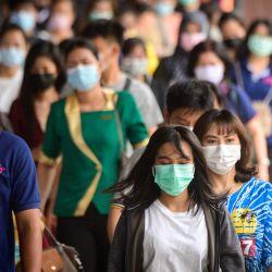 Los viajeros con máscaras protectoras caminan por el muelle de Pratunam en Bangkok, después de que el gobierno impusiera restricciones estrictas, incluida una multa de 20.000 THB (525 euros, 636 USD) por no usar una máscara en público tras el reciente brote de Covid-19. Casos de coronavirus en Tailandia. | Foto:Mladen Antonov / AFP
