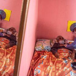 Un trabajador de salud revisa a María Tafur antes de inocularla con una dosis de la vacuna Pfizer-BioNTech contra el COVID-19, en su casa del distrito El Agustino de Lima. | Foto:Ernesto Benavides / AFP