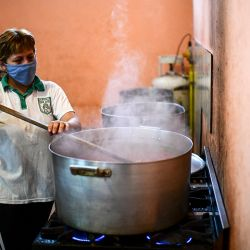 A woman cooks at a soup kitchen at the Puerta de Hierro neighborhood, in La Matanza municipality, Buenos Aires province, Argentina, on April 12, 2021.