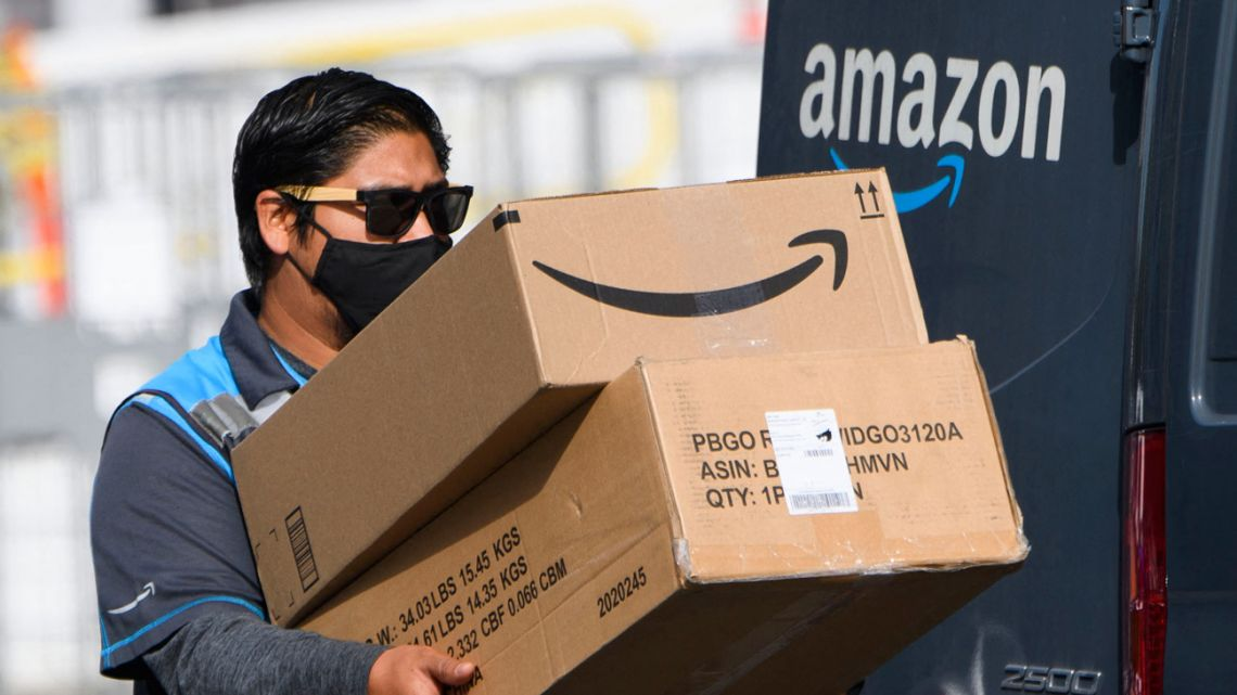 In this file photo taken on February 02, 2021, an Amazon delivery driver carries boxes into a van outside of a distribution facility in Hawthorne, California.