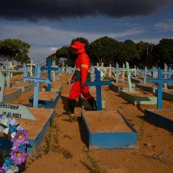 Un sepulturero camina entre las tumbas de las víctimas del COVID-19 en el cementerio de Nossa Senhora Aparecida en Manaus, estado de Amazonas, Brasil. - Brasil, con una población de 212.000.000 de personas, superó el jueves las 400.000 muertes por COVID-19 , y ocupa el segundo lugar en número solo después de EE. UU. | Foto:Michael Dantas / AFP
