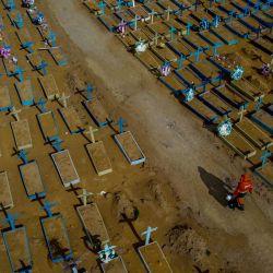 Vista aérea de un sepulturero caminando entre las tumbas de las víctimas del COVID-19 en el cementerio de Nossa Senhora Aparecida en Manaus, estado de Amazonas, Brasil. | Foto:Michael Dantas / AFP