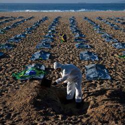 Un manifestante del grupo activista de derechos humanos de Río de Paz cava una tumba simbólica frente a filas de bolsas que simbolizan bolsas para cadáveres en la playa de Copacabana, durante una protesta contra el manejo del gobierno brasileño de la pandemia de coronavirus, en Río de Janeiro. - El grupo protestaba contra las crecientes cifras de muertes por COVID-19 en el país que ahora ha superado la cifra de 400.000.   Foto:Carl De Souza / AFP