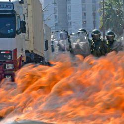 Chile, Iquique: Los neumáticos se queman y bloquean una calle durante una protesta de los trabajadores portuarios por el pago anticipado de una pensión debido a la pandemia del coronavirus. | Foto:Cristian Vivero Boornes / Agencia Uno / DPA