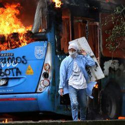 Un hombre camina frente a un autobús de transporte público en llamas durante una protesta contra un proyecto de reforma tributaria lanzado por el presidente colombiano Iván Duque, en Cali. | Foto:Paola Mafla / AFP