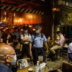 Los oficiales y la policía del Departamento de Alimentos e Higiene Ambiental y la policía se van después de inspeccionar la licencia de un restaurante y bar después de que reabrieron, en Lan Kwai Fong, un área popular para beber en Hong Kong. | Foto:Anthony Wallace / AFP