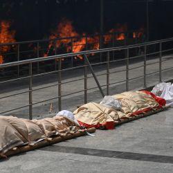 Los cuerpos de las víctimas del coronavirus Covid-19 se alinearon antes de la cremación en un campo de cremación en Nueva Delhi. | Foto:Money Sharma / AFP