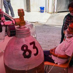 Un paciente con coronavirus Covid-19 respira con la ayuda de oxígeno proporcionado por un Gurdwara, un lugar de culto para los sijs, debajo de una carpa instalada a lo largo de una carretera en Ghaziabad. | Foto:Prakash Singh / AFP