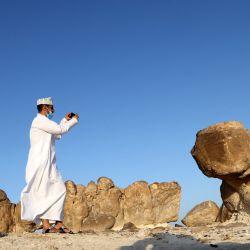 Un omaní toma fotografías en el Rock Garden en la ciudad portuaria de Duqm en la provincia de al-Wusta en el centro-este de Omán, a unos 540 kilómetros al sur de la capital. - El Rock Garden en Duqm es uno de los principales sitios geológicos, con formaciones rocosas inusuales de hace 46 millones de años. | Foto:Karim Sahib / AFP