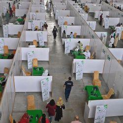 Las personas se reúnen para vacunarse con la vacuna contra el coronavirus Sinopharm Covid-19 de fabricación china en un campo de vacunación organizado en el centro de exposiciones en Lahore. | Foto:Arif Ali / AFP