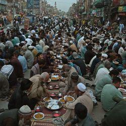 Los devotos musulmanes rompen su ayuno Iftar a lo largo de una carretera durante el mes sagrado del Ramadán en Rawalpindi. | Foto:Farooq Naeem / AFP
