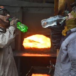 Los trabajadores beben agua durante un freno en una acería en Lahore. | Foto:Arif Ali / AFP