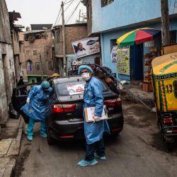 Trabajadores de salud llegan para inocular a ancianos con dosis de la vacuna Pfizer-BioNTech contra COVID-19, a su casa del distrito El Agustino en Lima. | Foto:Ernesto Benavides / AFP