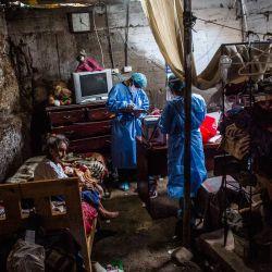Trabajadores de la salud se preparan para inocular a Tomasa Olguin con una dosis de la vacuna Pfizer-BioNTech contra COVID-19, en su casa del distrito El Agustino de Lima.   Foto:Ernesto Benavides / AFP