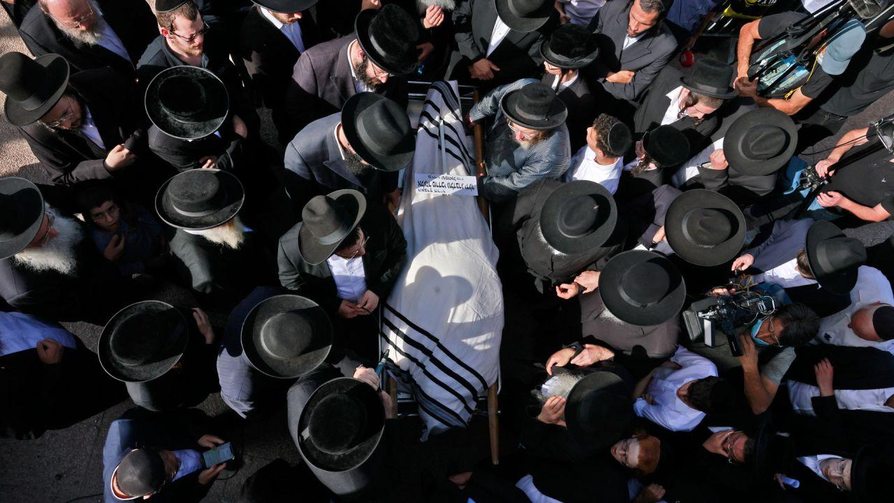 Hombres judíos ultraortodoxos participan en una ceremonia fúnebre en Jerusalén por una víctima de una estampida nocturna durante una reunión religiosa en el norte de Israel. | Foto:Menahem Kahana / AFP