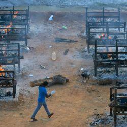 Un empresario de pompas fúnebres lleva un tronco de madera en medio de piras ardientes de las víctimas que murieron por el coronavirus Covid-19 en un crematorio al aire libre establecido para las víctimas del coronavirus dentro de una cantera de granito desaparecida en las afueras de Bangalore.   Foto:Manjunath Kiran / AFP