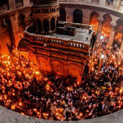 Los cristianos ortodoxos se reúnen con velas encendidas alrededor del Edículo, que tradicionalmente se cree que es el lugar del entierro de Jesucristo, durante la ceremonia del Fuego Santo en la iglesia del Santo Sepulcro de Jerusalén.   Foto:Emmanuel Dunand / AFP