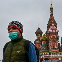 Un hombre con una máscara facial camina cerca de la torre Spasskaya del Kremlin y la catedral de San Basilio en Moscú, mientras la ciudad se prepara para celebrar el 76 aniversario de la victoria sobre la Alemania nazi durante la Guerra Mundial. II.   Foto:Yuri Kadobnov / AFP